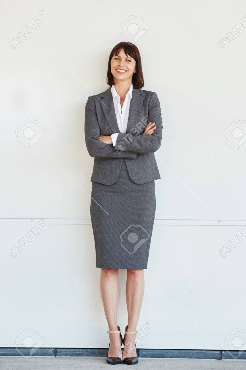 Full body portrait of professional business woman standing with arms crossed by white wall - 66843536
