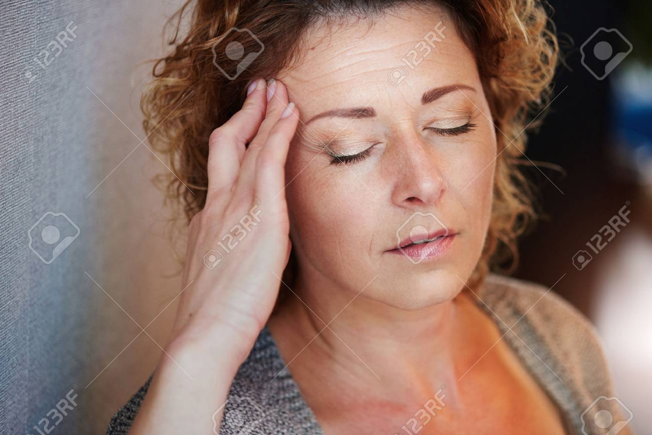 Close up portrait of older woman with hand to head in pain - 66843596