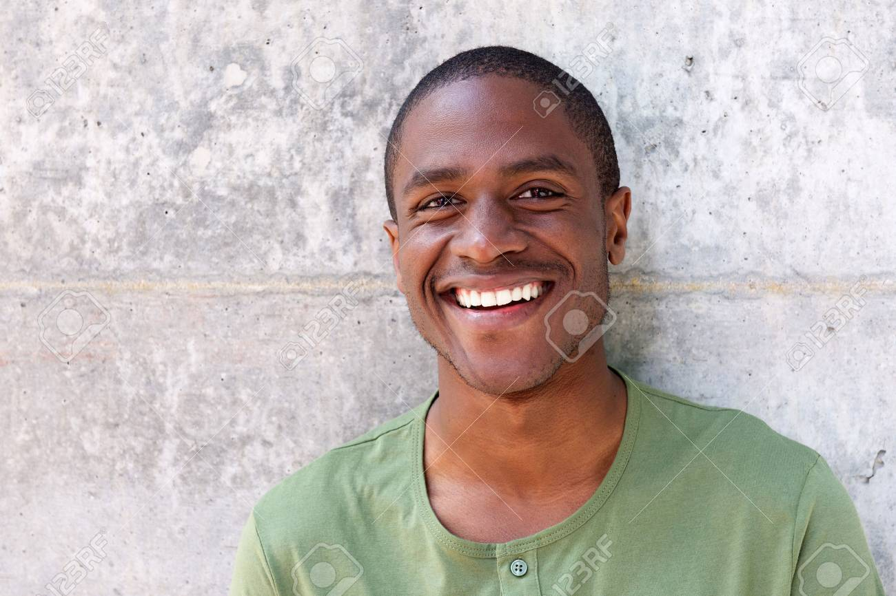 Close up portrait of cheerful young black man smiling against wall - 67048334