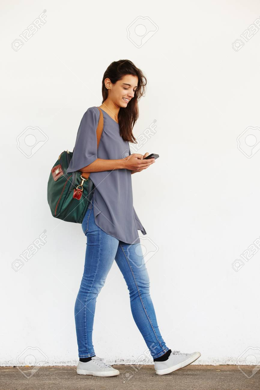 Full length portrait of beautiful young woman walking outside and reading text message on her mobile phone - 67625037