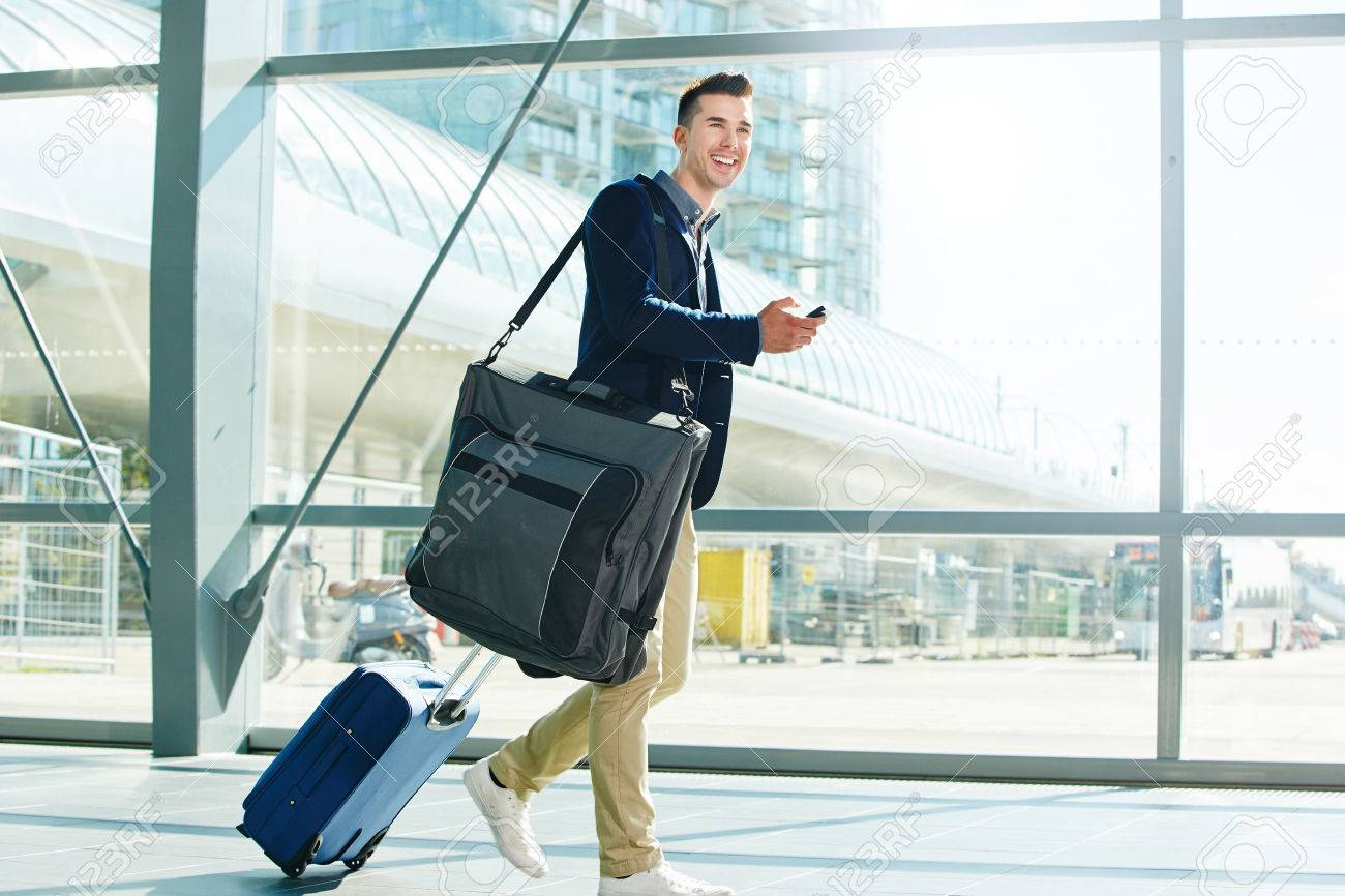 Full body portrait of man walking with luggage and phone in station smiling - 68850454