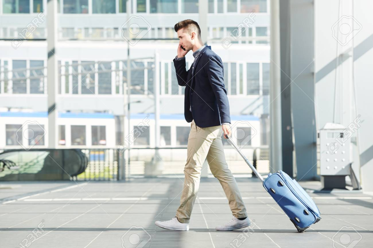 Full length side portrait of business man walking with luggage on telephone call at station - 68850459