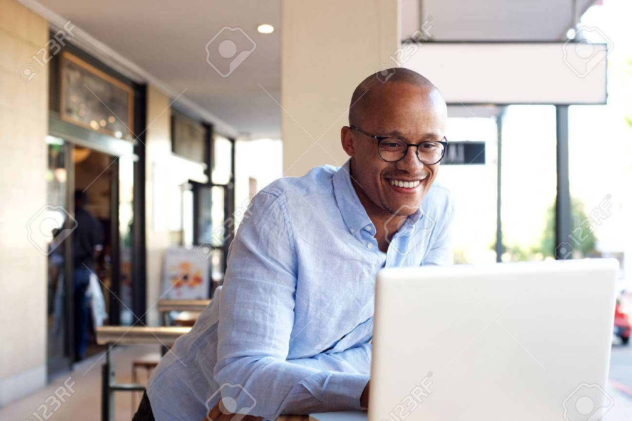 Portrait of handsome african businessman working with laptop - 69300071