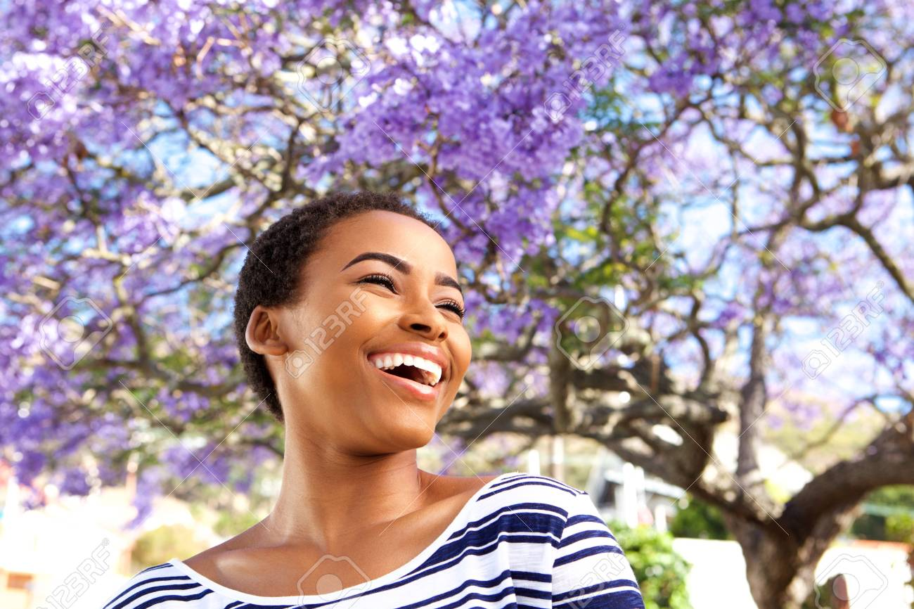 Portrait of attractive young black woman laughing outdoors by flower tree - 71517809