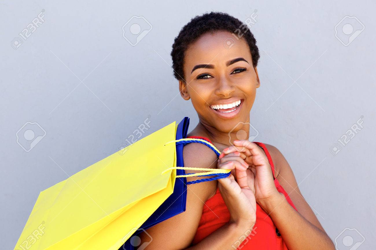 Close up portrait of young woman smiling with shopping bags - 71517852