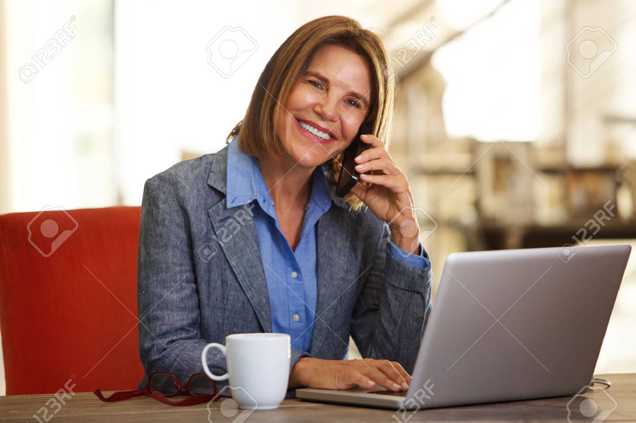 Portrait of smiling business woman sitting at desk with phone and laptop - 72425447