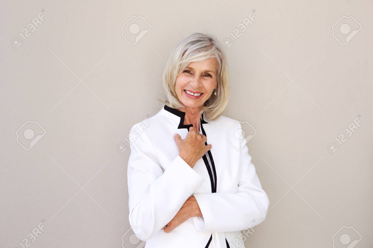 Portrait of beautiful older woman smiling and standing by wall - 74022112