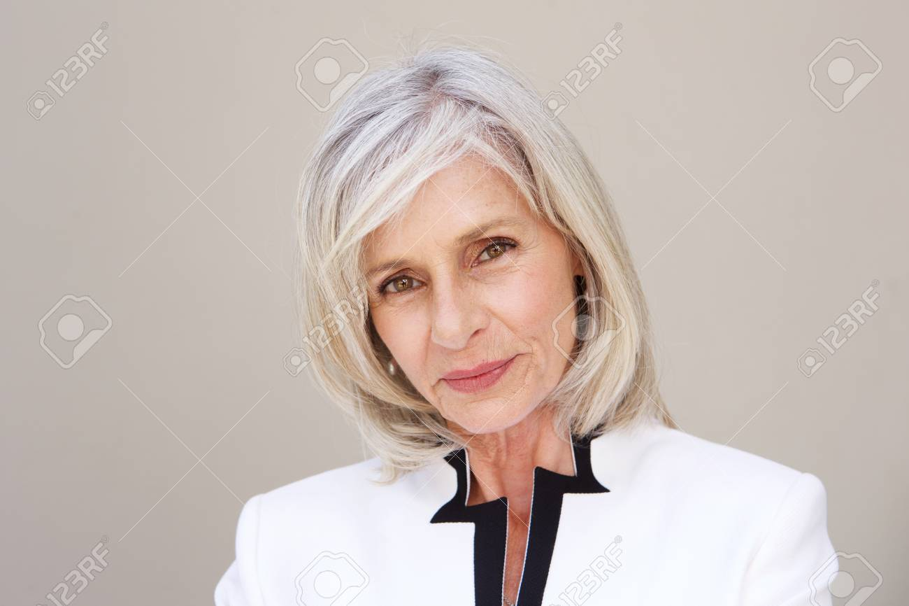 Close up portrait of beautiful older woman staring standing by wall - 74022131