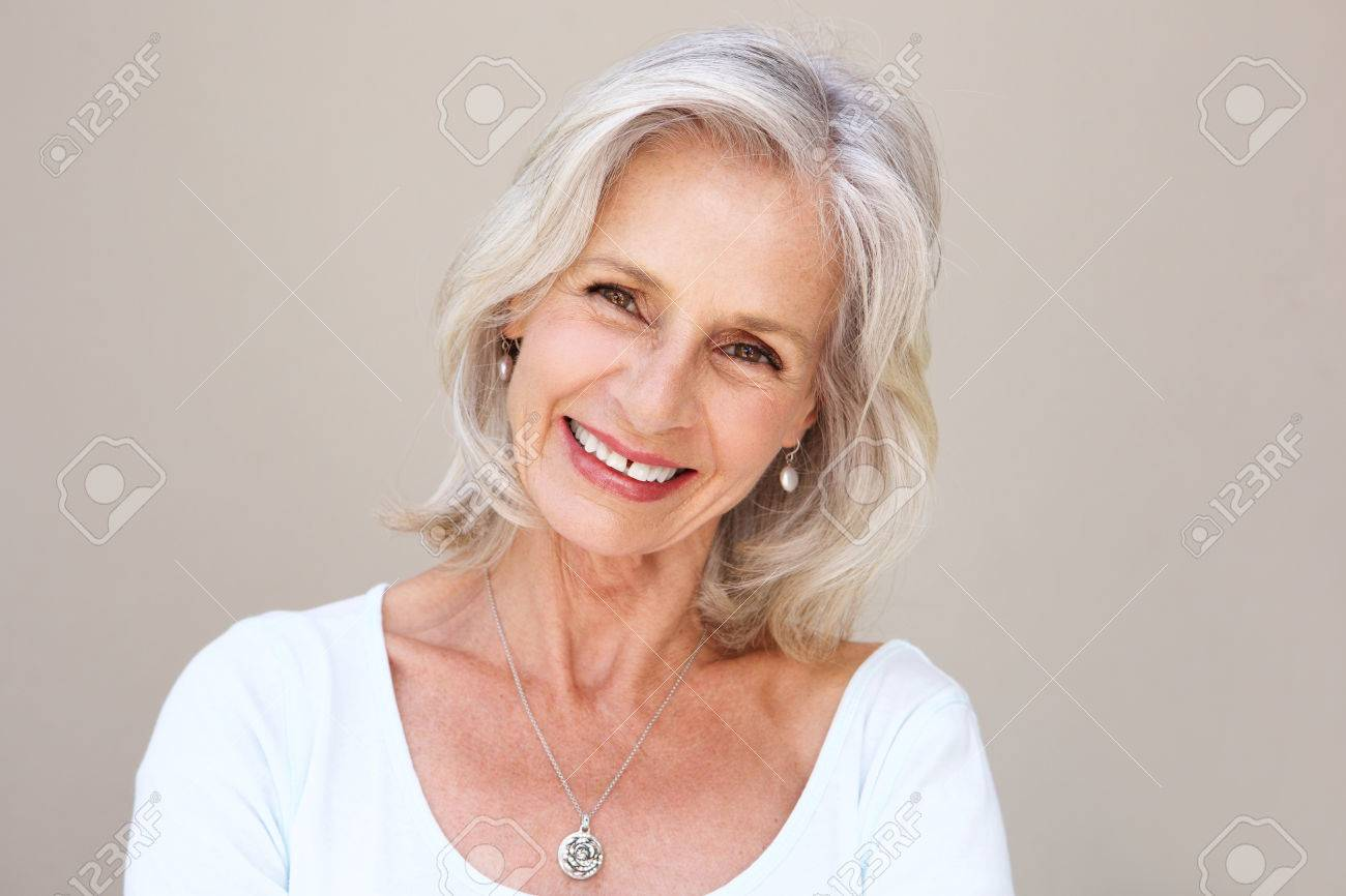 Close up portrait of beautiful older woman smiling and standing by wall - 74021919