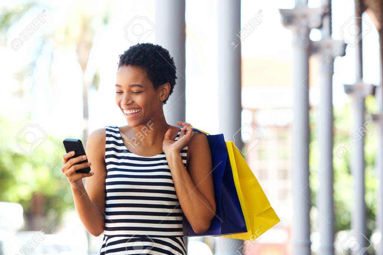 Portrait of happy young african american woman walking with cellphone and shopping bags - 75916537