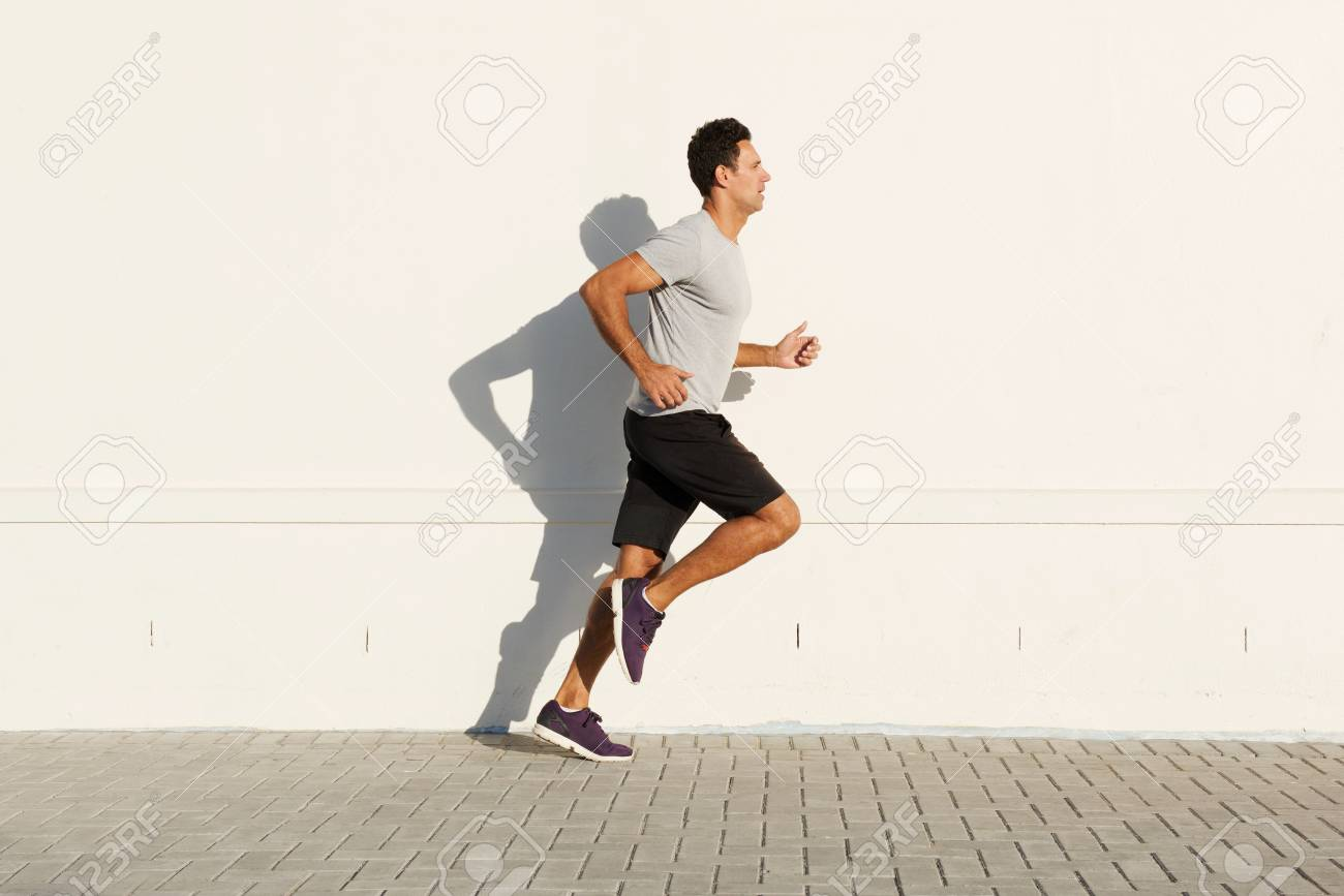 Side portrait of middle age man running by white wall - 77621552