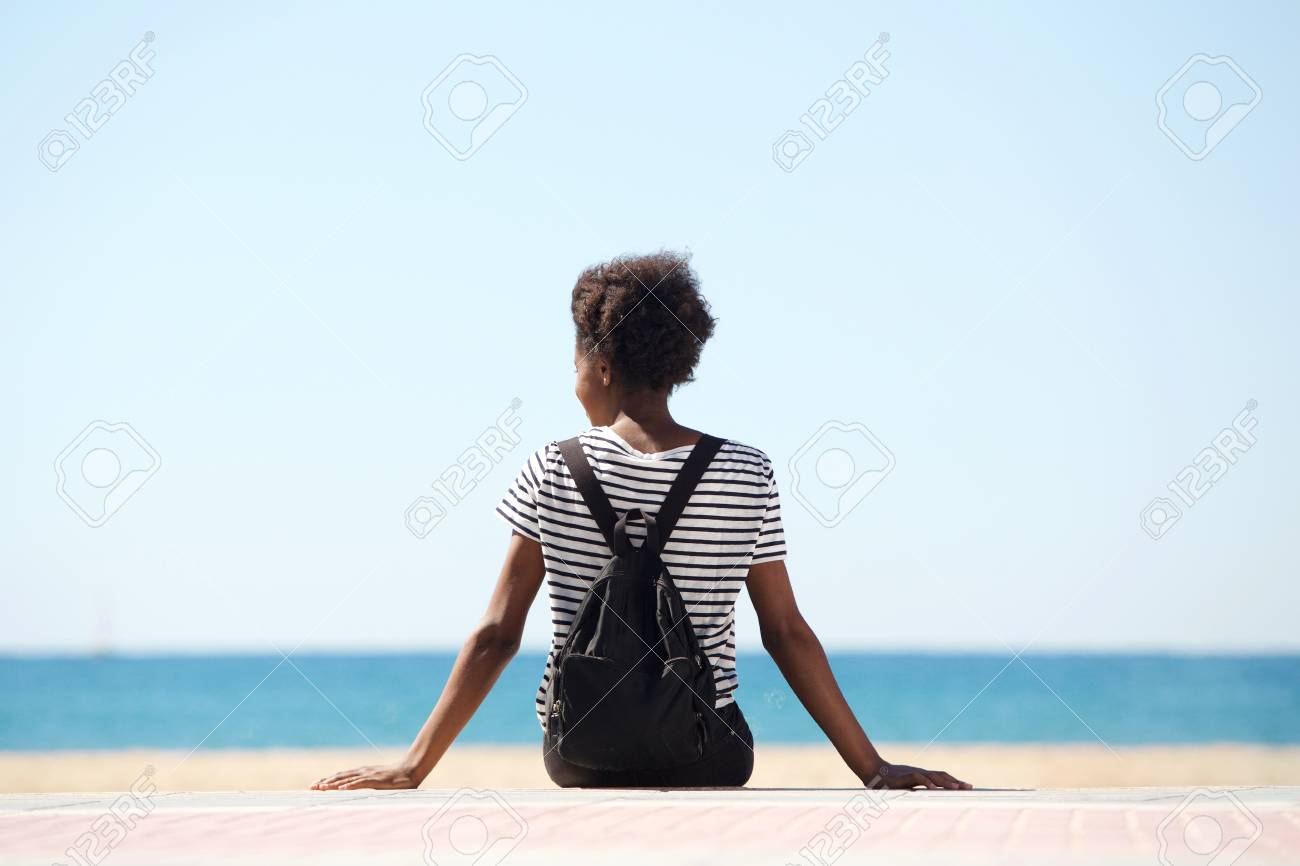 Rear view portrait of young woman sitting by the beach on summer day - 81319700