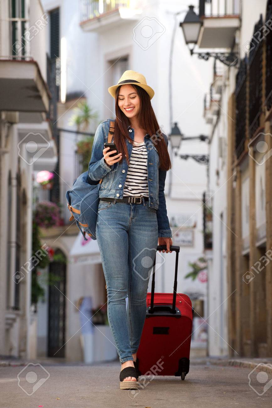 Full length portrait of woman walking on street with luggage holding mobile phone - 81809609