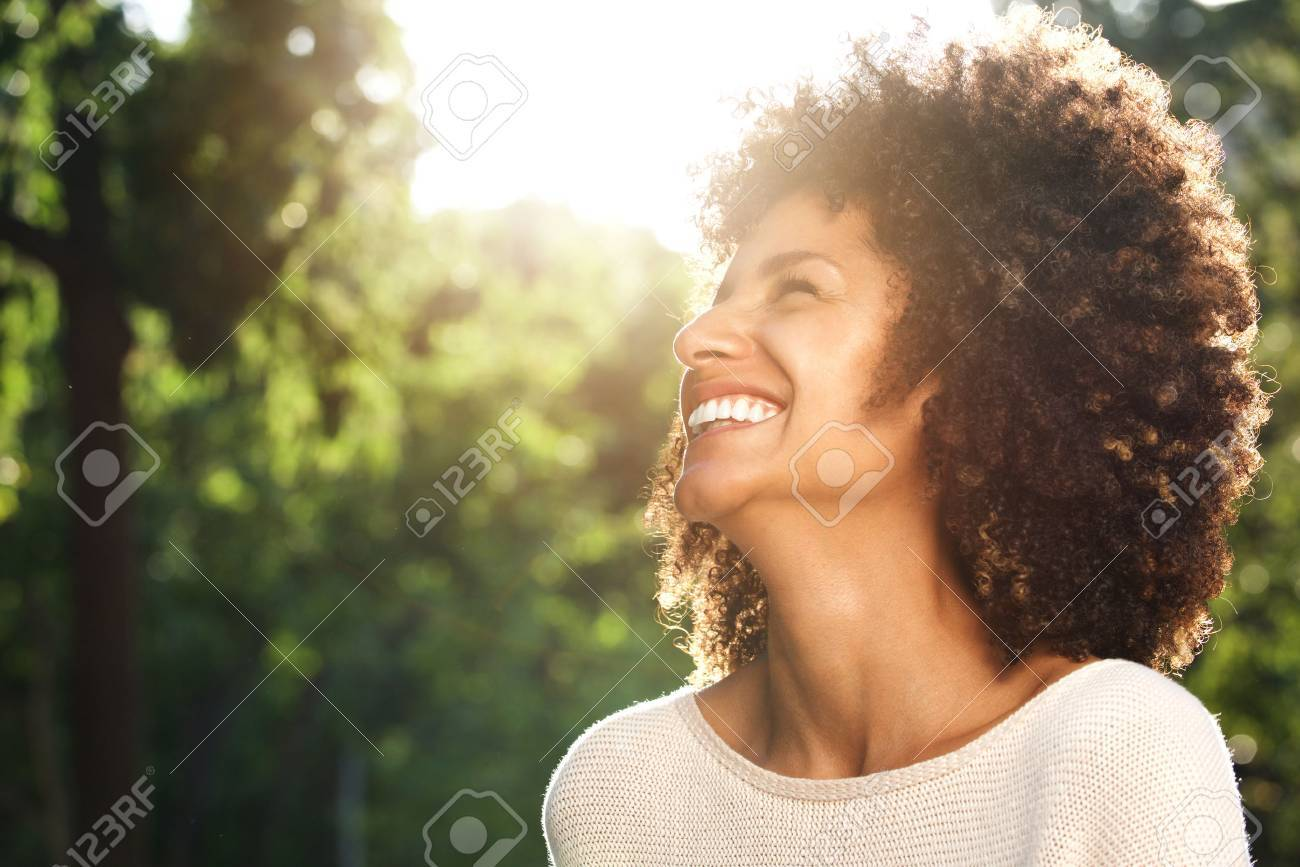 Close up side portrait of beautiful confident woman laughing in nature - 84917433