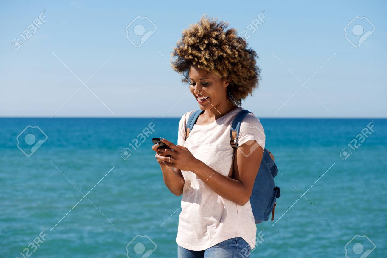 Portrait of smiling african woman on the beach reading text message on smart phone - 85260980
