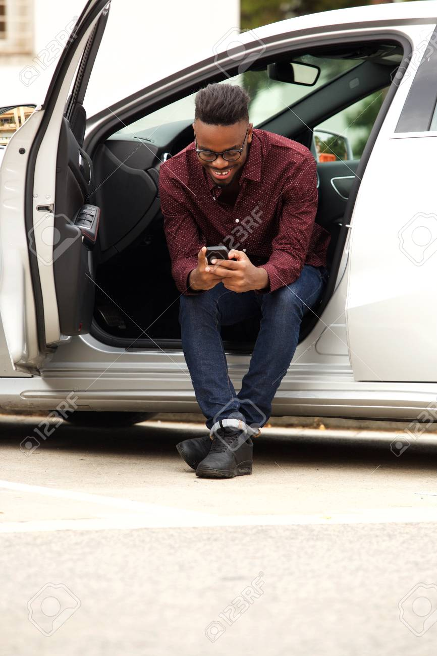 Portrait of african american man sitting in car sending text message - 93987257