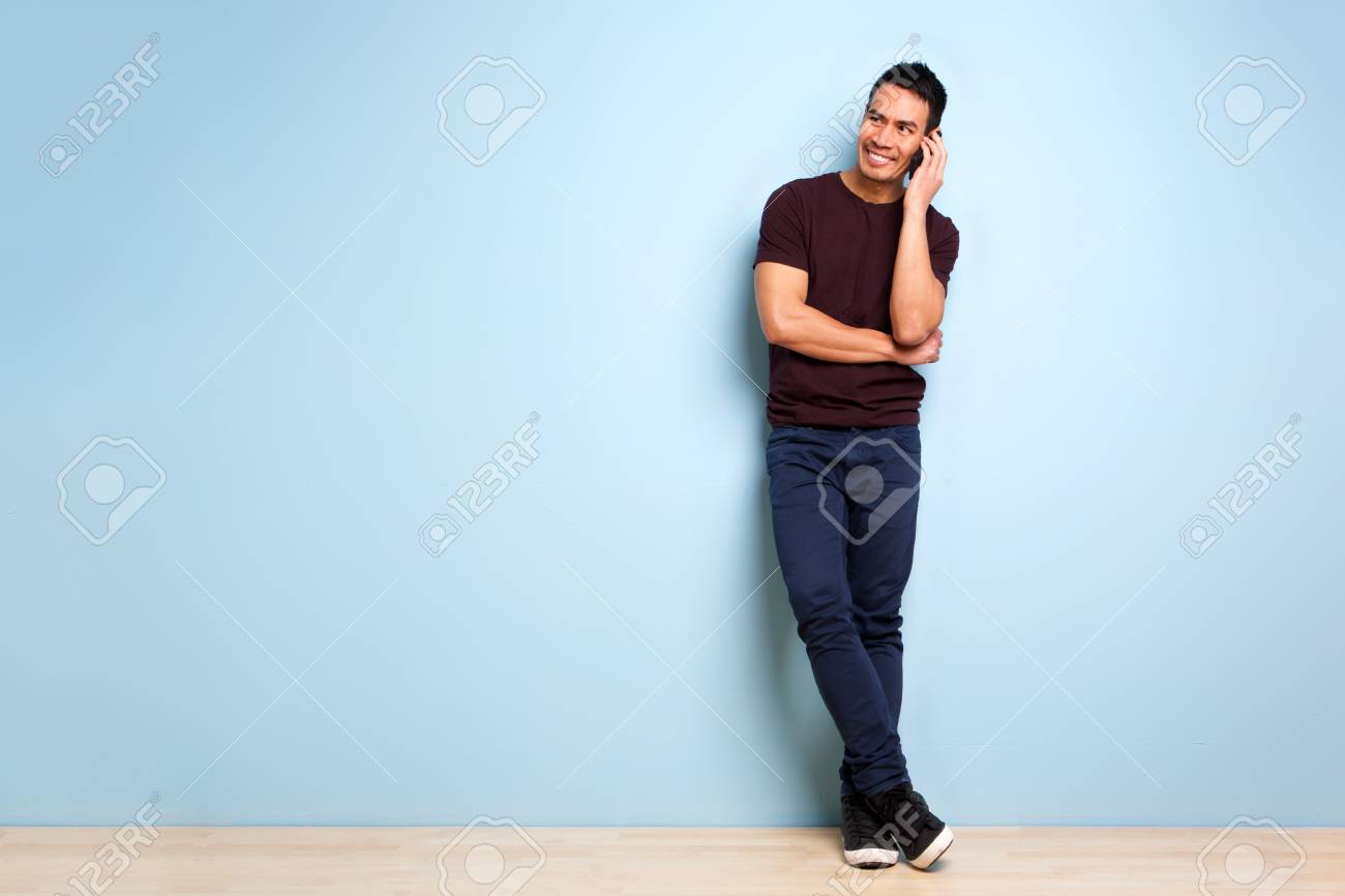 Full body portrait of stylish mature asian man standing by blue wall and making a phone call - 102339871