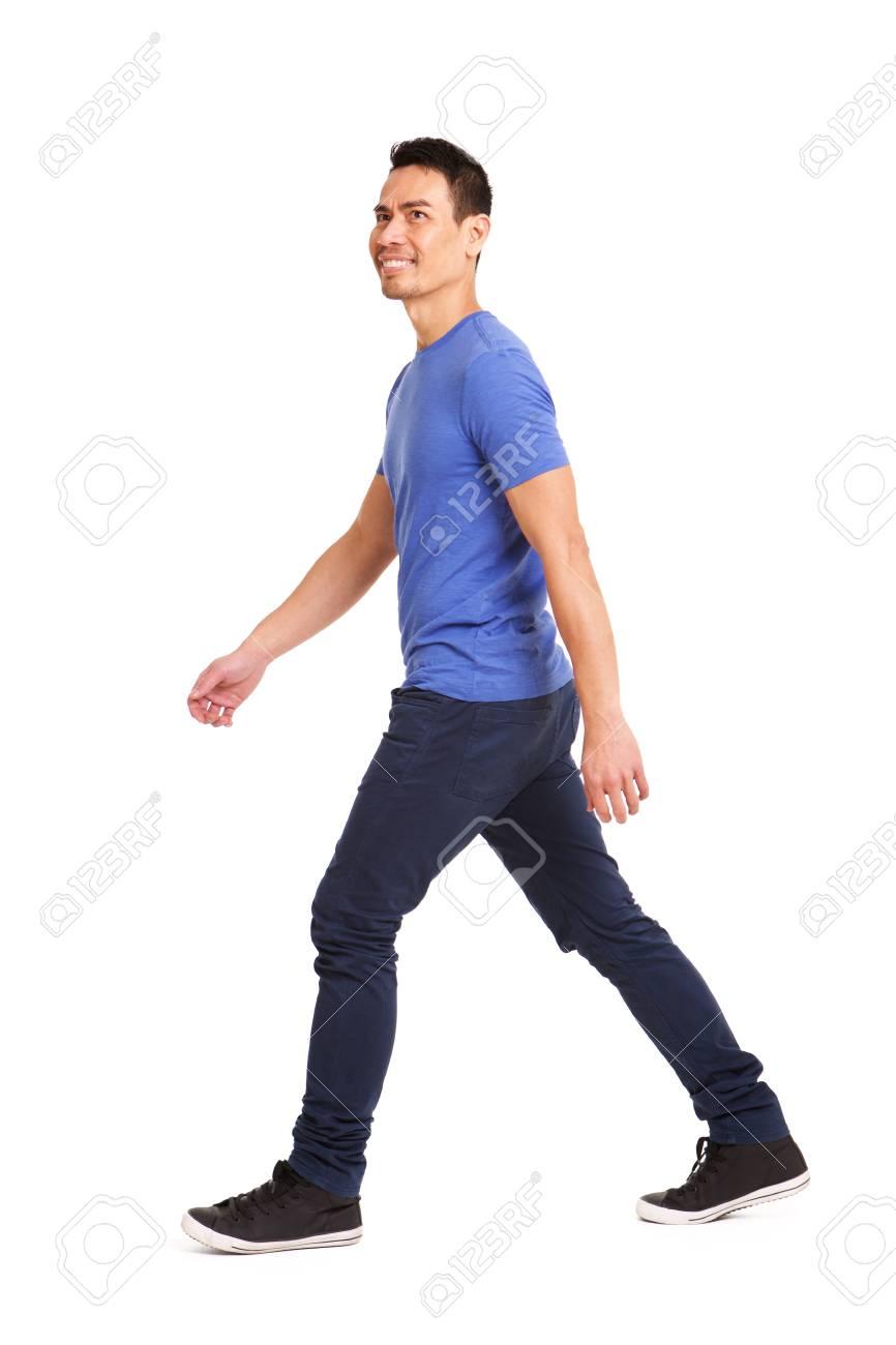 Full length side portrait of happy asian man walking over white background - 101337603