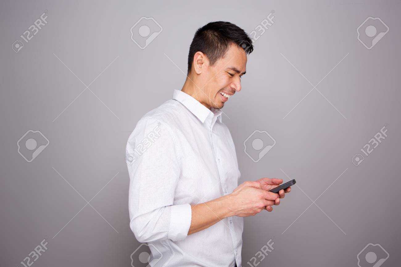 Portrait of smiling middle aged man reading text message on his mobile phone on gray background - 101233929