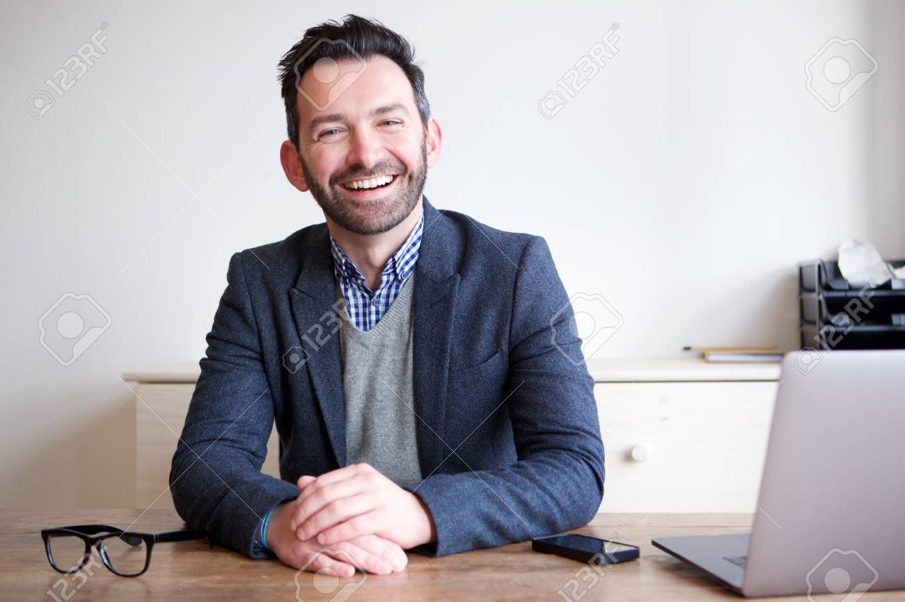 Portrait of smiling businessman sitting in office - 102938638