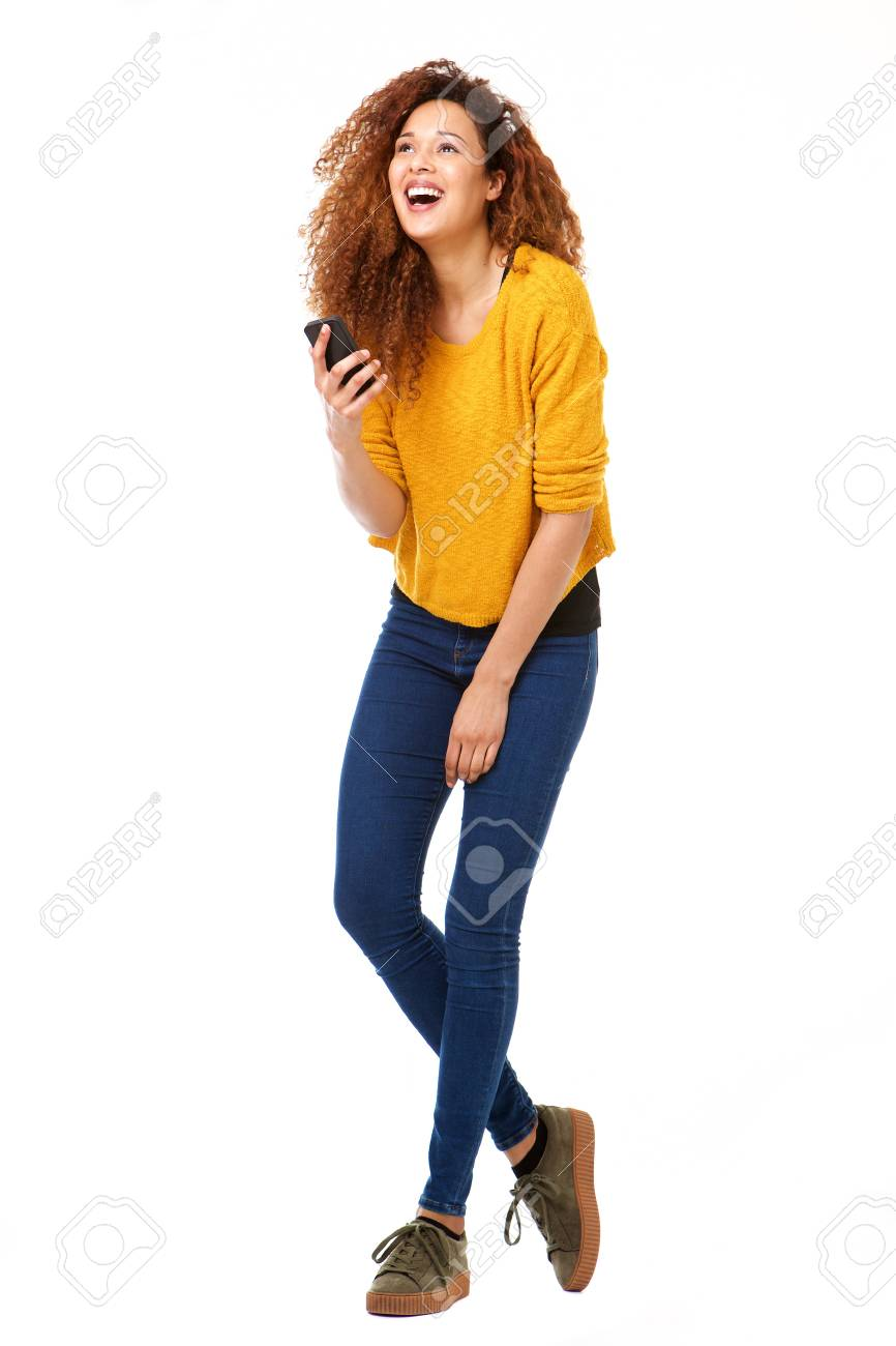 Full body portrait of happy woman with smart phone laughing against isolated white background - 103927028