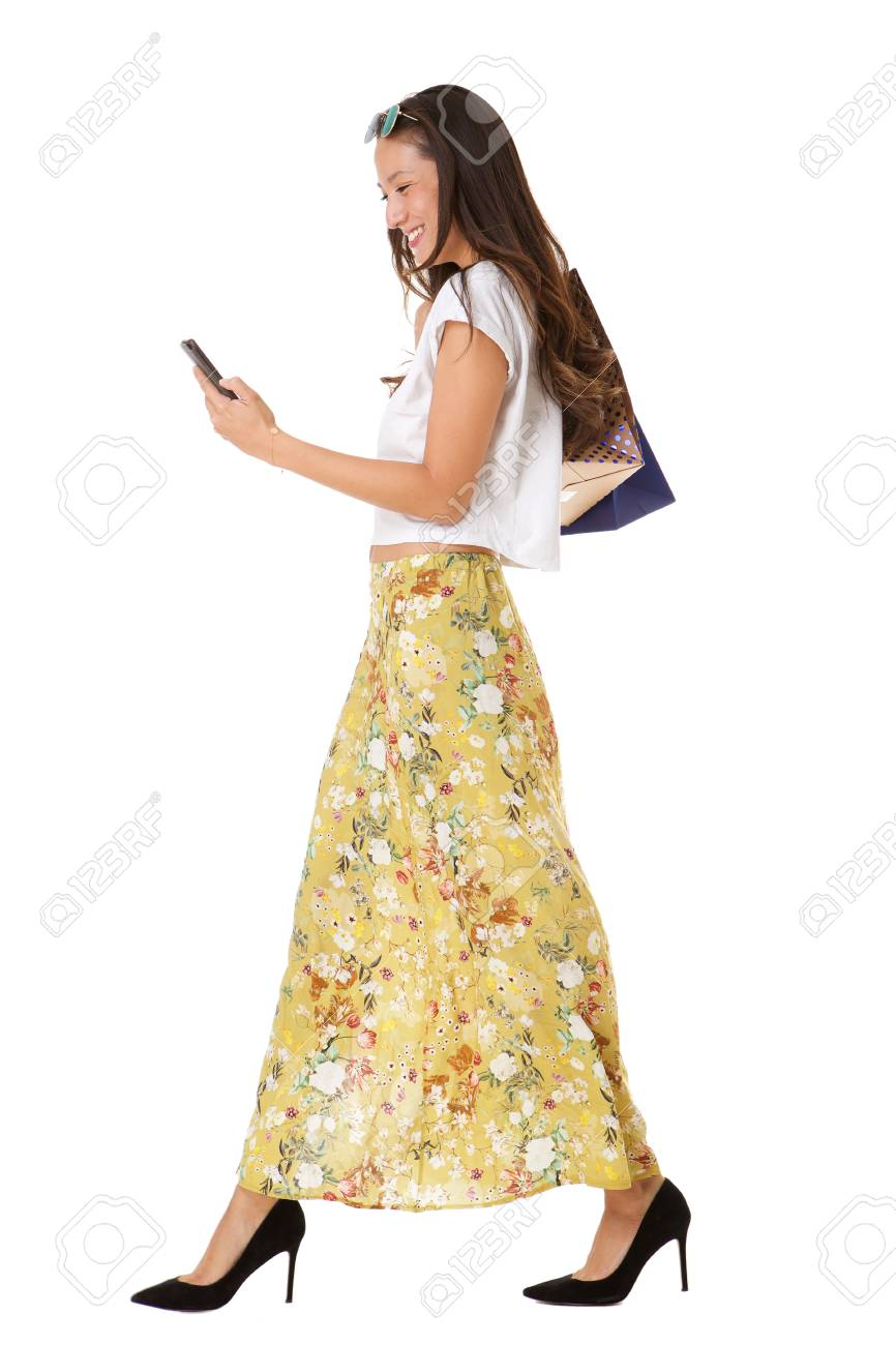 Full length side portrait of smiling asian woman walking with mobile phone and shopping bags against isolated white background - 113179718