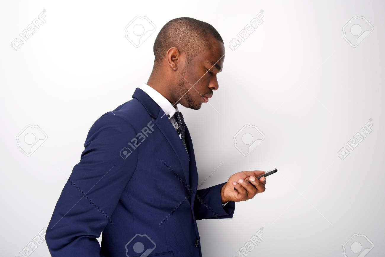 Side portrait of young black businessman looking at mobile phone - 118849673
