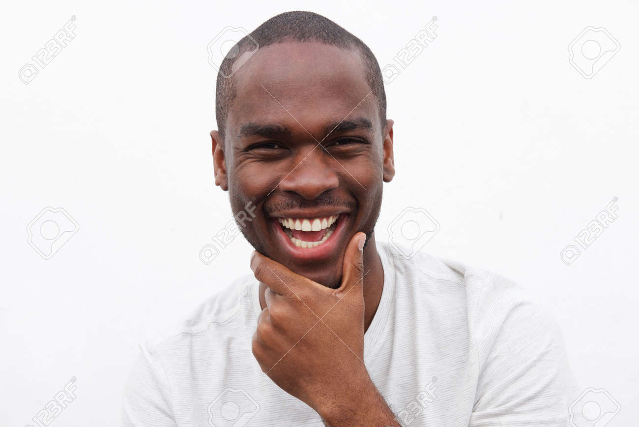 Close up portrait of handsome young black man smiling with hand to chin - 121039812