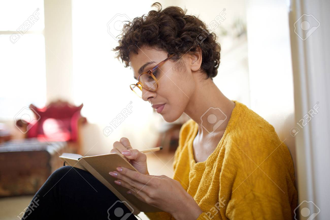 Close up portrait of young african american woman with glasses writing in book - 122879622