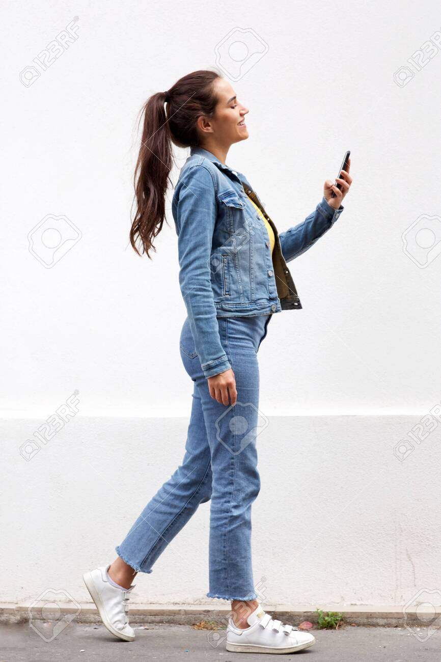 Full length portrait of young woman with brown hair walking and looking at mobile phone by white wall - 129649795