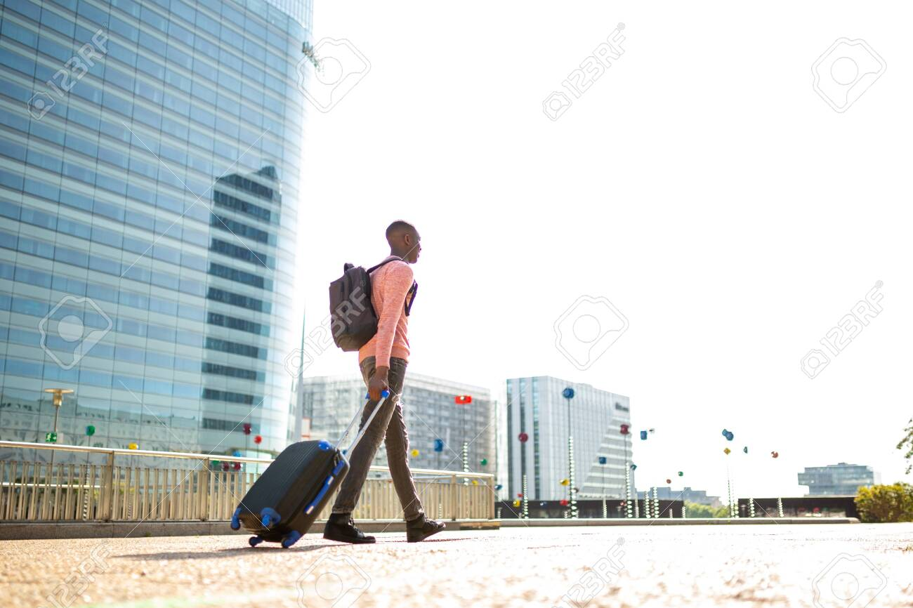 Full length portrait of young black man walking with suitcase in city - 130816866