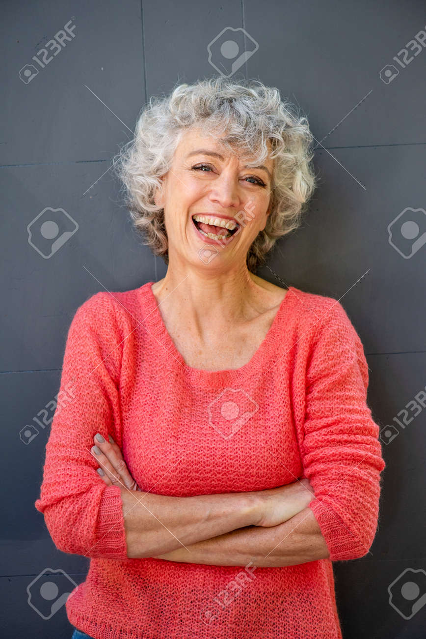 Front portrait of attractive middle aged woman laughing with arms crossed - 133515654