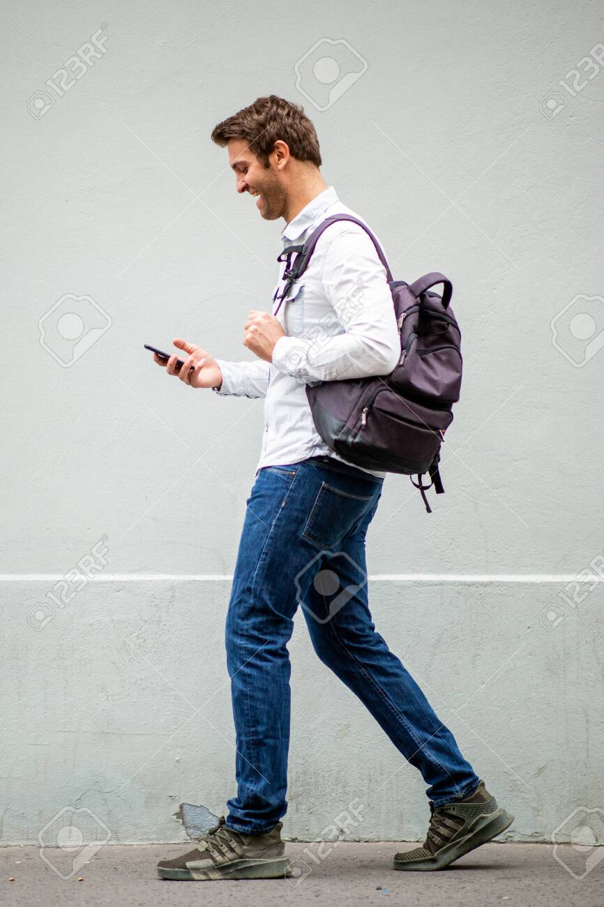Full body portrait of happy travel man with bag looking at mobile phone by gray wall - 137765213