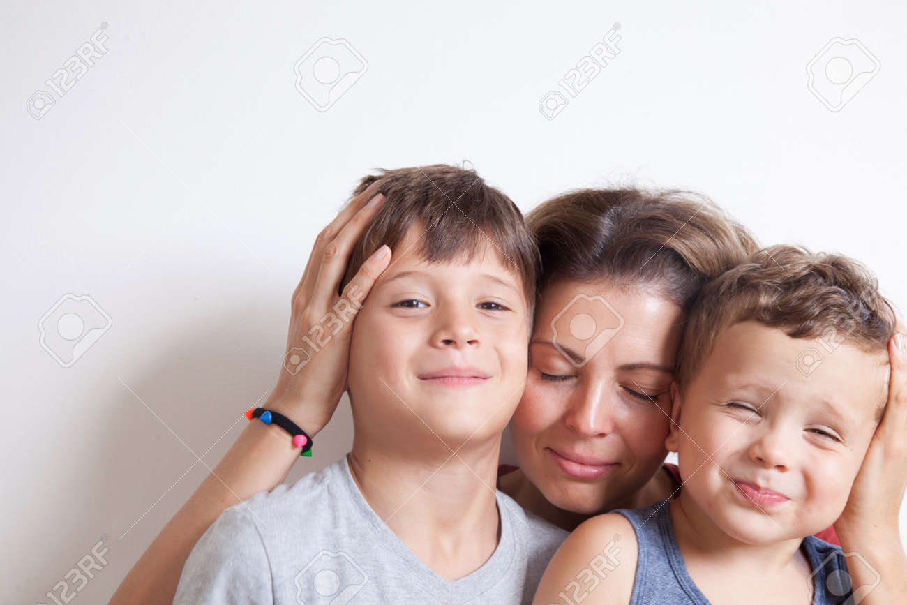 Portrait of happy mother with cute kids boy sitting on a light background. Happy family concept. - 156193086