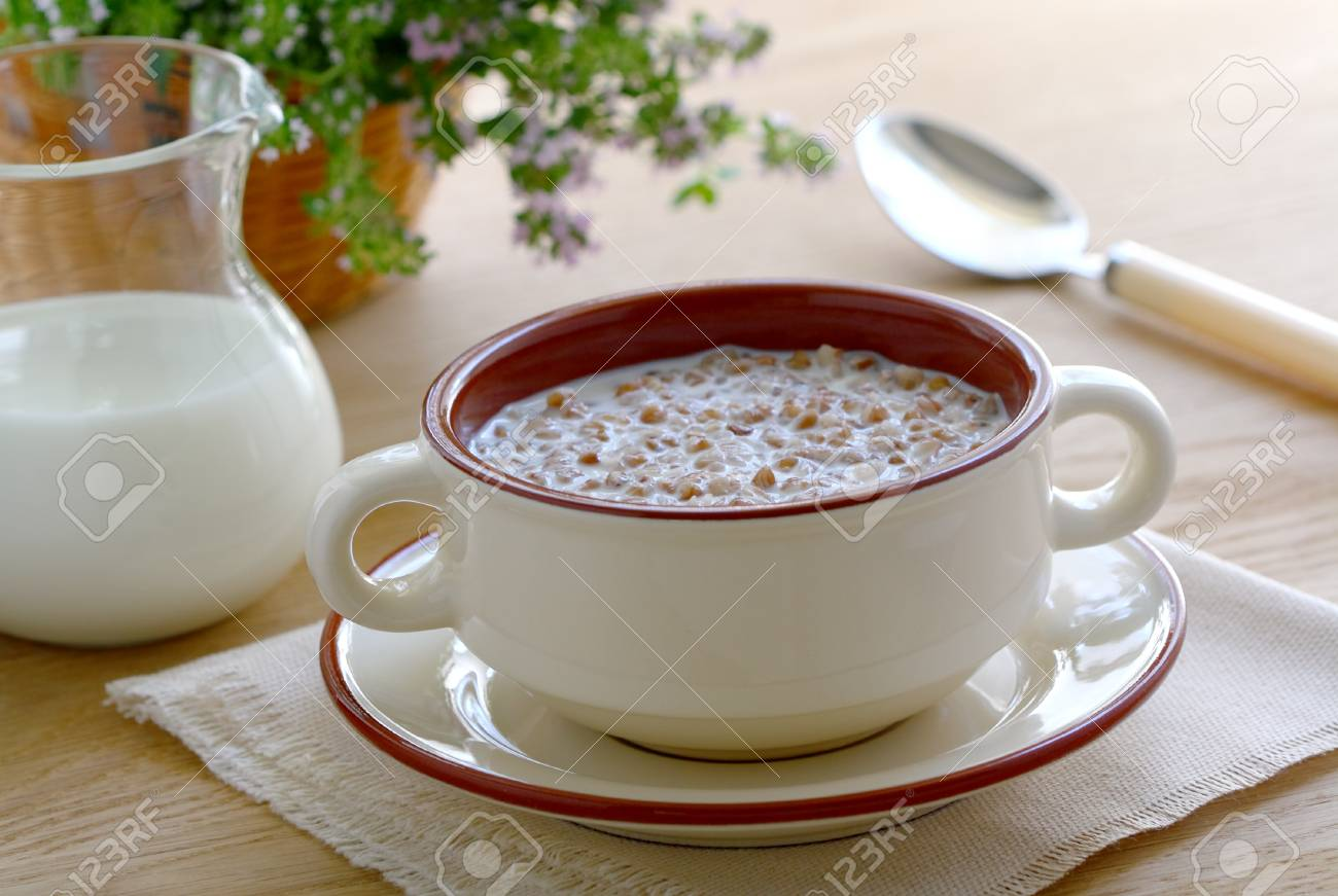 Buckwheat porridge with milk in a bowl on wooden table Stock Photo - 14494311