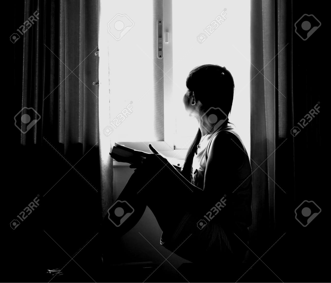 The silhouette of stressed and depressed woman worried about her studies in black and white. processed in low key light - 125949314