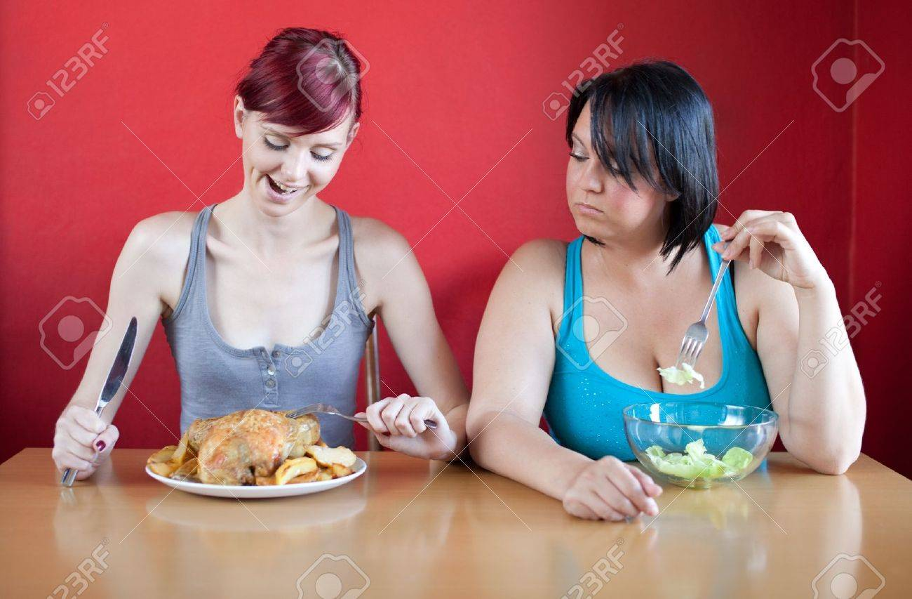 Tailored diet. Skinny woman is happy because she can eat huge meals, while the overweight woman is looking sadly at her because she has to eat just a few leaves of lattuce. Stock Photo - 9779471