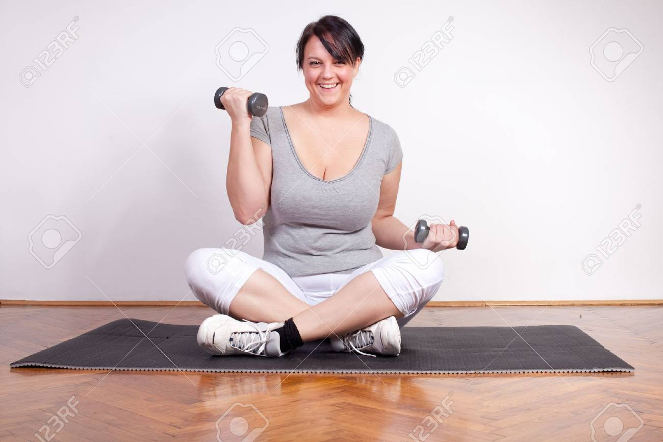 Happy overweight woman lifting weights Stock Photo - 11913246