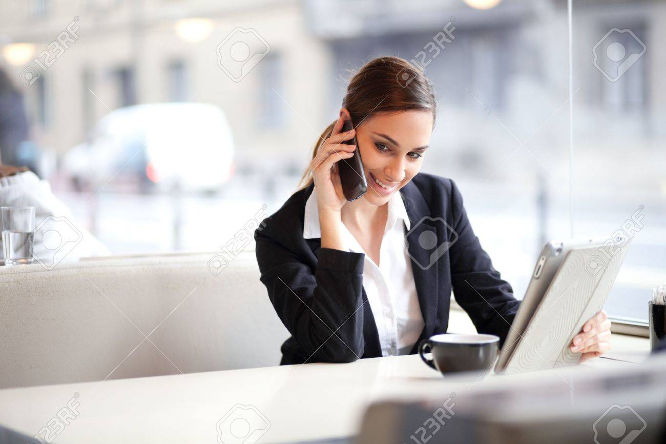 Candid image of a businesswoman talking on the phone in a coffee shop Stock Photo - 17537345