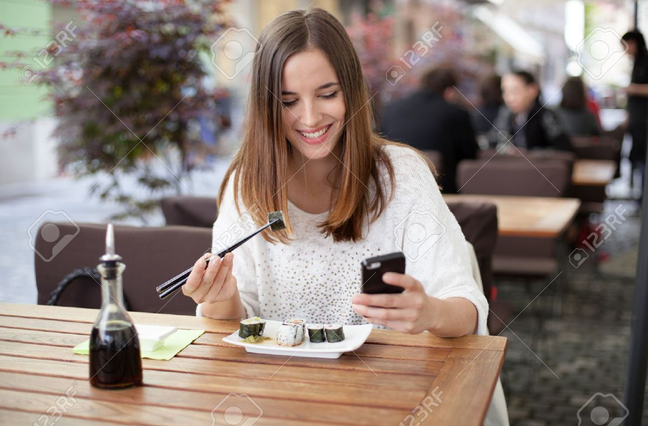Happy young woman eating sushi in a restaurant and using mobile phone Stock Photo - 19754643