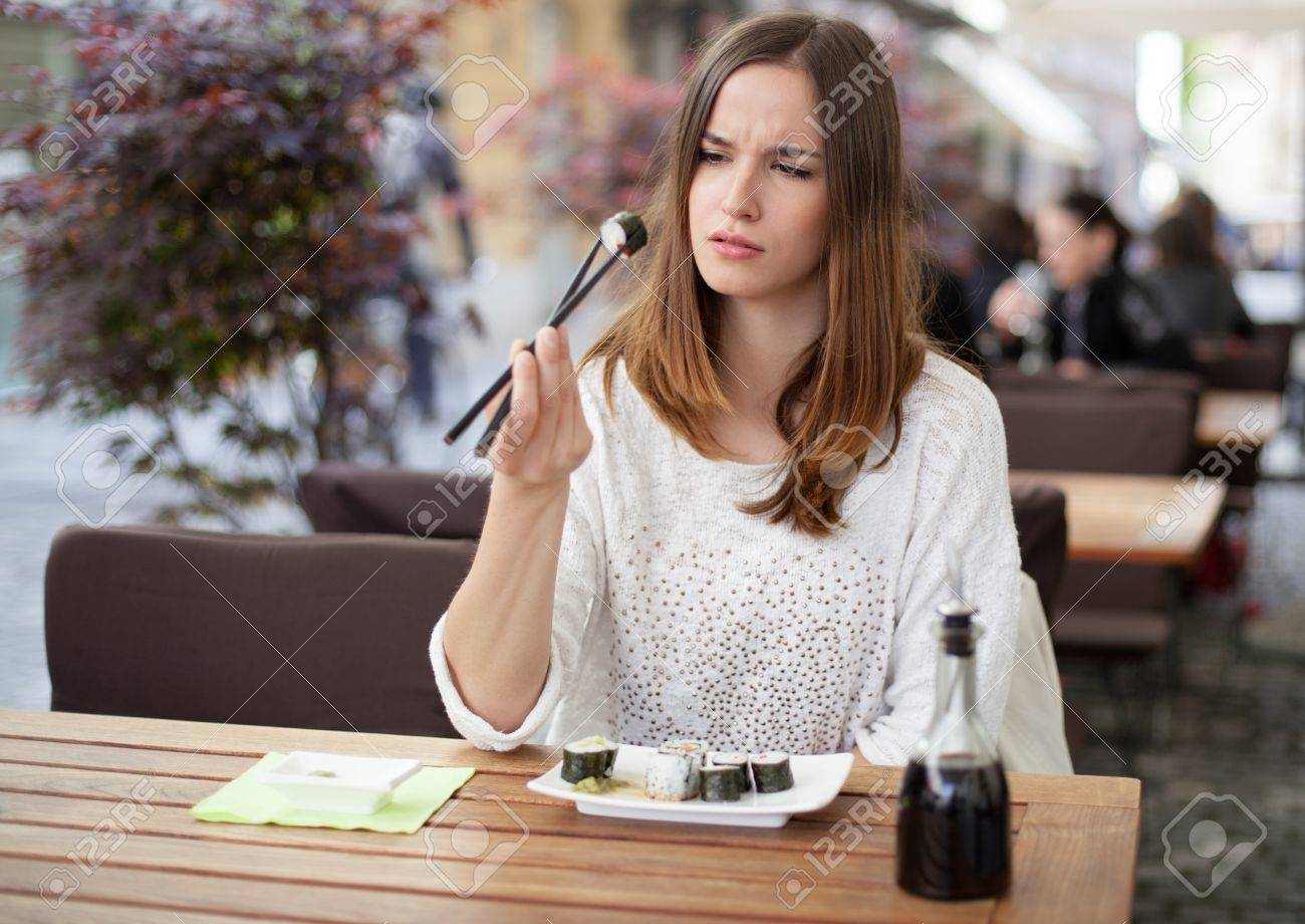 Young woman unsure about eating sushi Stock Photo - 19980996