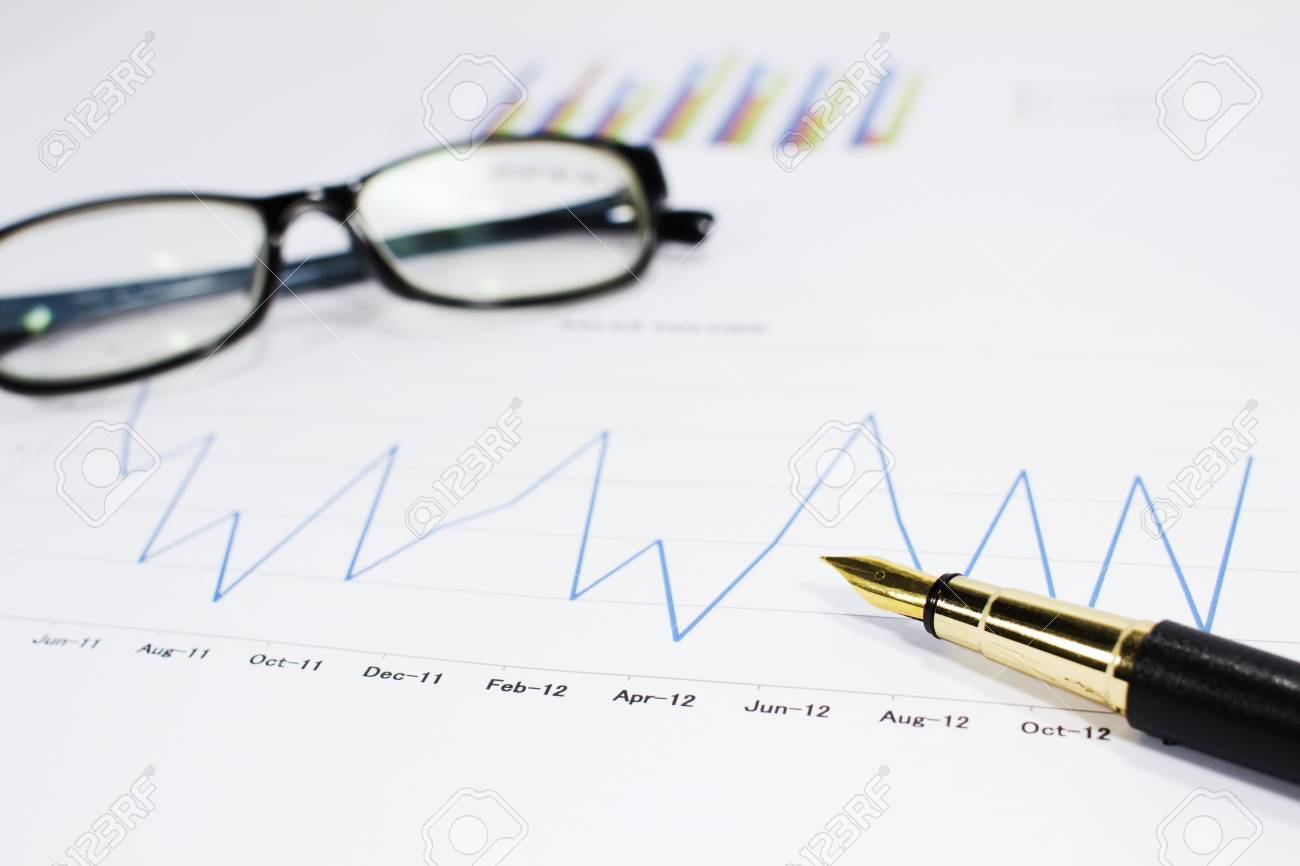 sales volume charts on the table with pen - 15494223