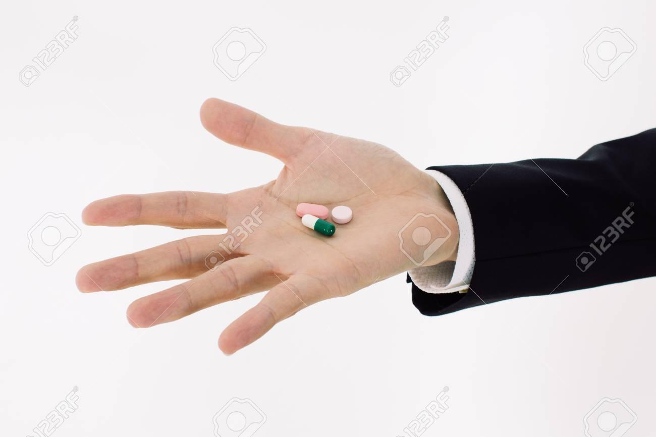 pills on mens hand - 15513561