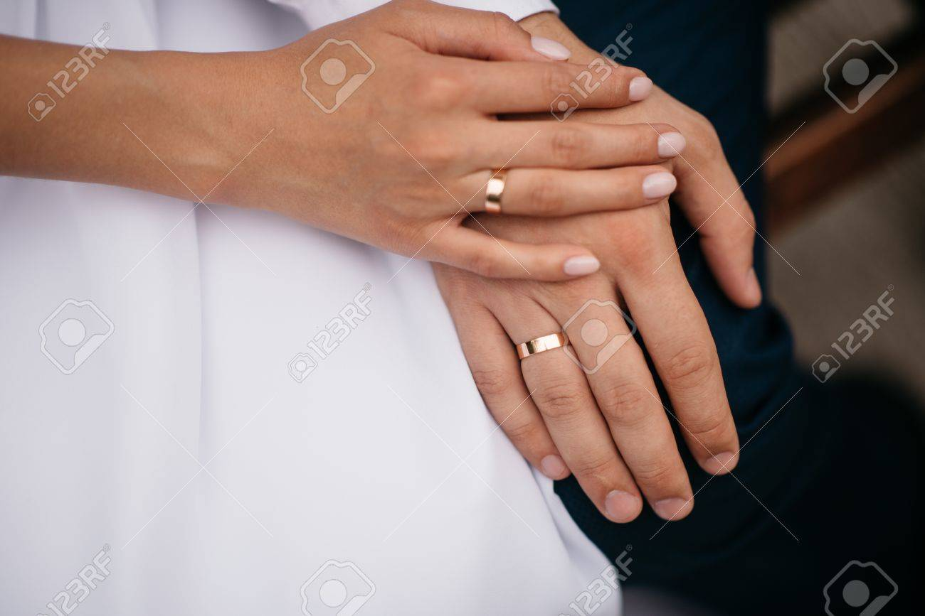 Newly Wed Couple S Hands With Gold Wedding Rings Stock Photo