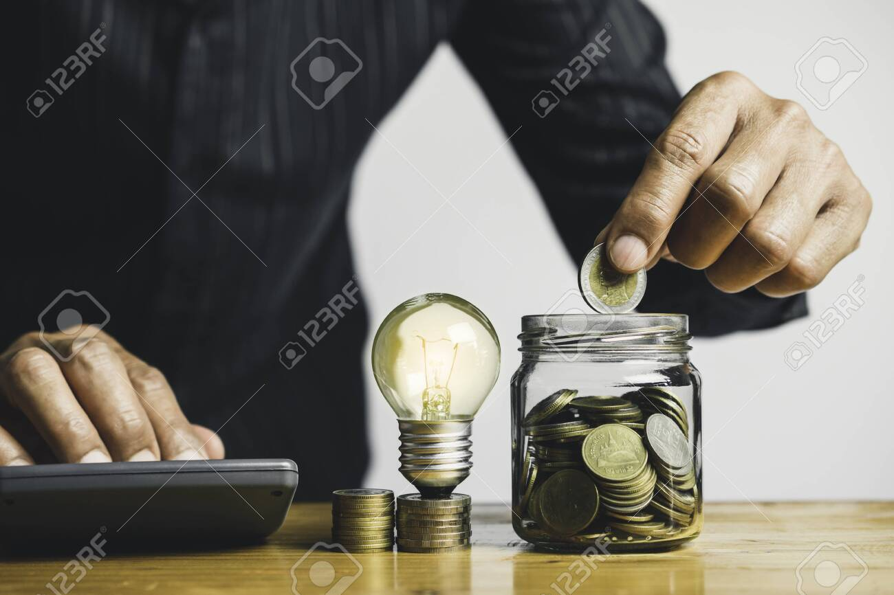 Business man holding light bulb on the desk in office and writing on note book it for financial,accounting,energy,idea concept. - 138239082