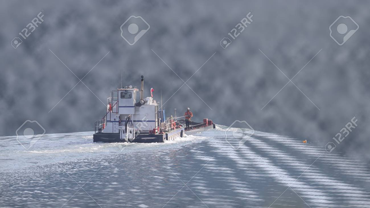 34f5bc62cc Stock Photo - Tug boat pushing a barge on a river in low visibility, foggy  conditions