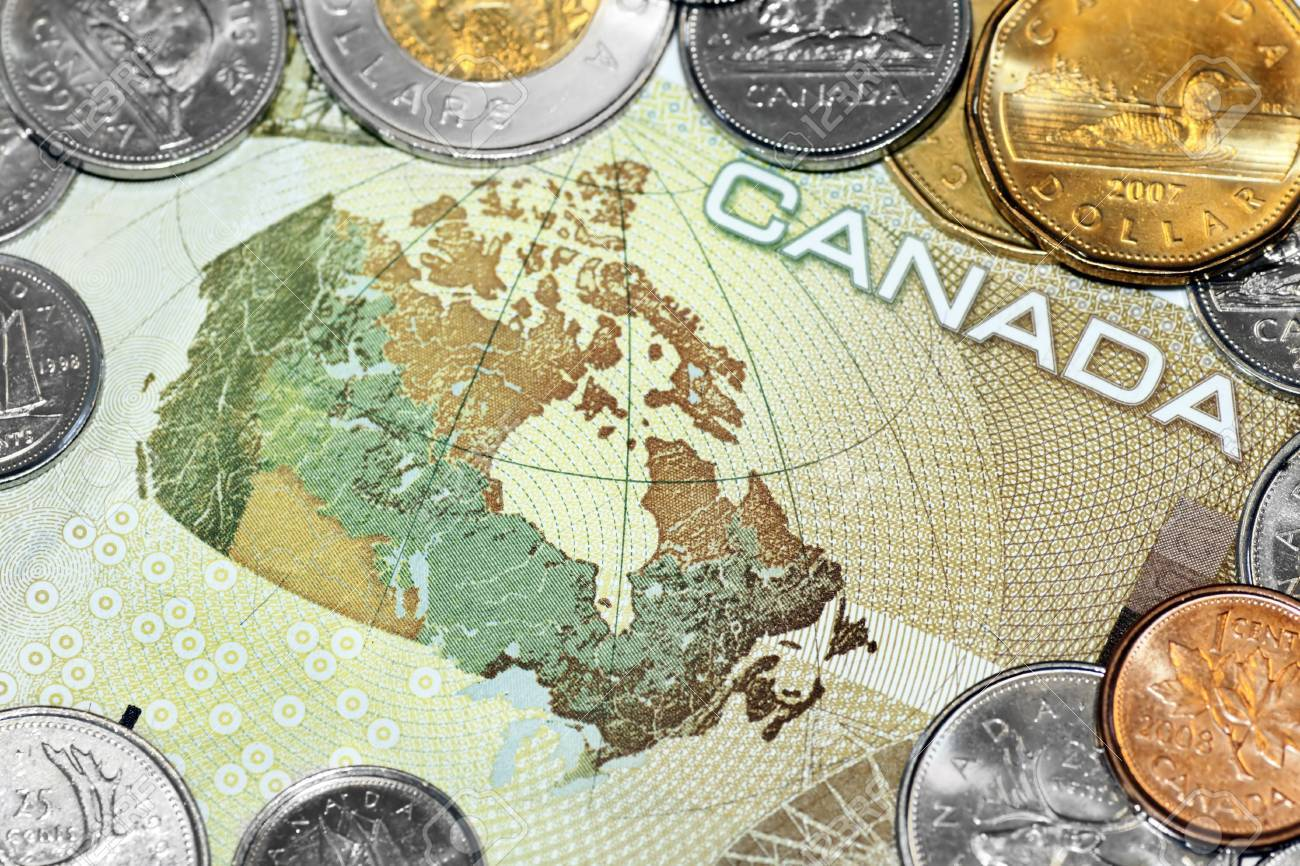 Close up of a one hundred canadian dollar bill showing the map of Canada, surrounded by loony and tuney coins. Stock Photo - 8753260