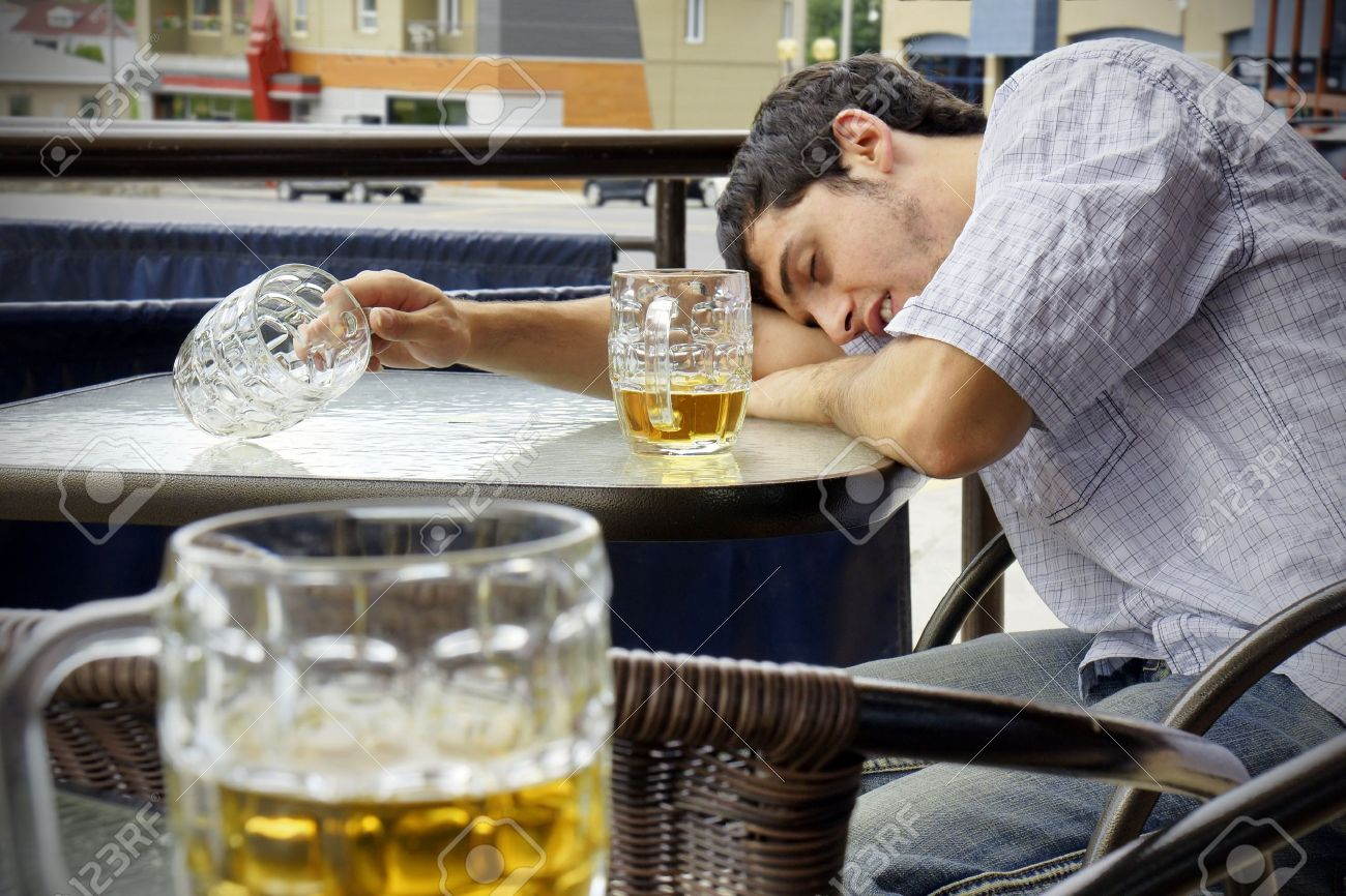 Young man passed out drunk with beer bocks on the glass table of an outdoor terrace: perfect for alcoholism, student hazing, beer binging and other related concepts. Stock Photo - 11368379