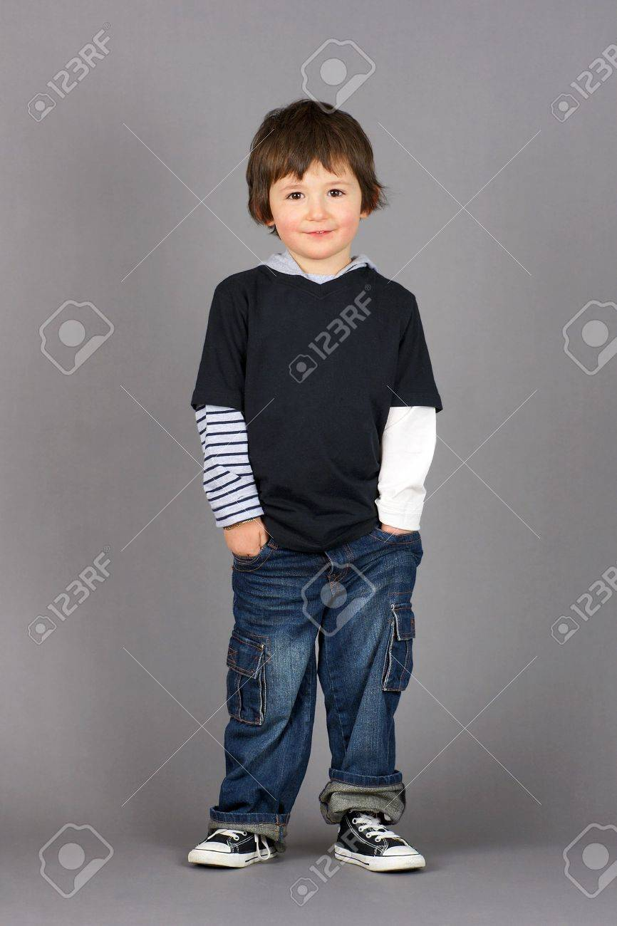 Cute and hip little preschooler boy with big brown eyes smiling with hands in his jeans pockets over grey background. Stock Photo - 12064222