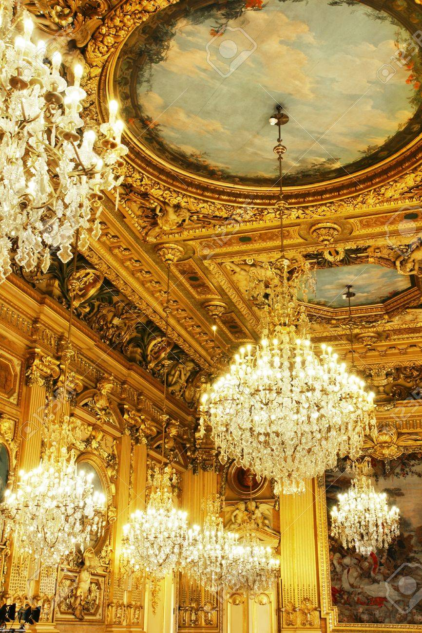 opulent cristal chandeliers and gold leaves wood carved and painted ceiling part of a french